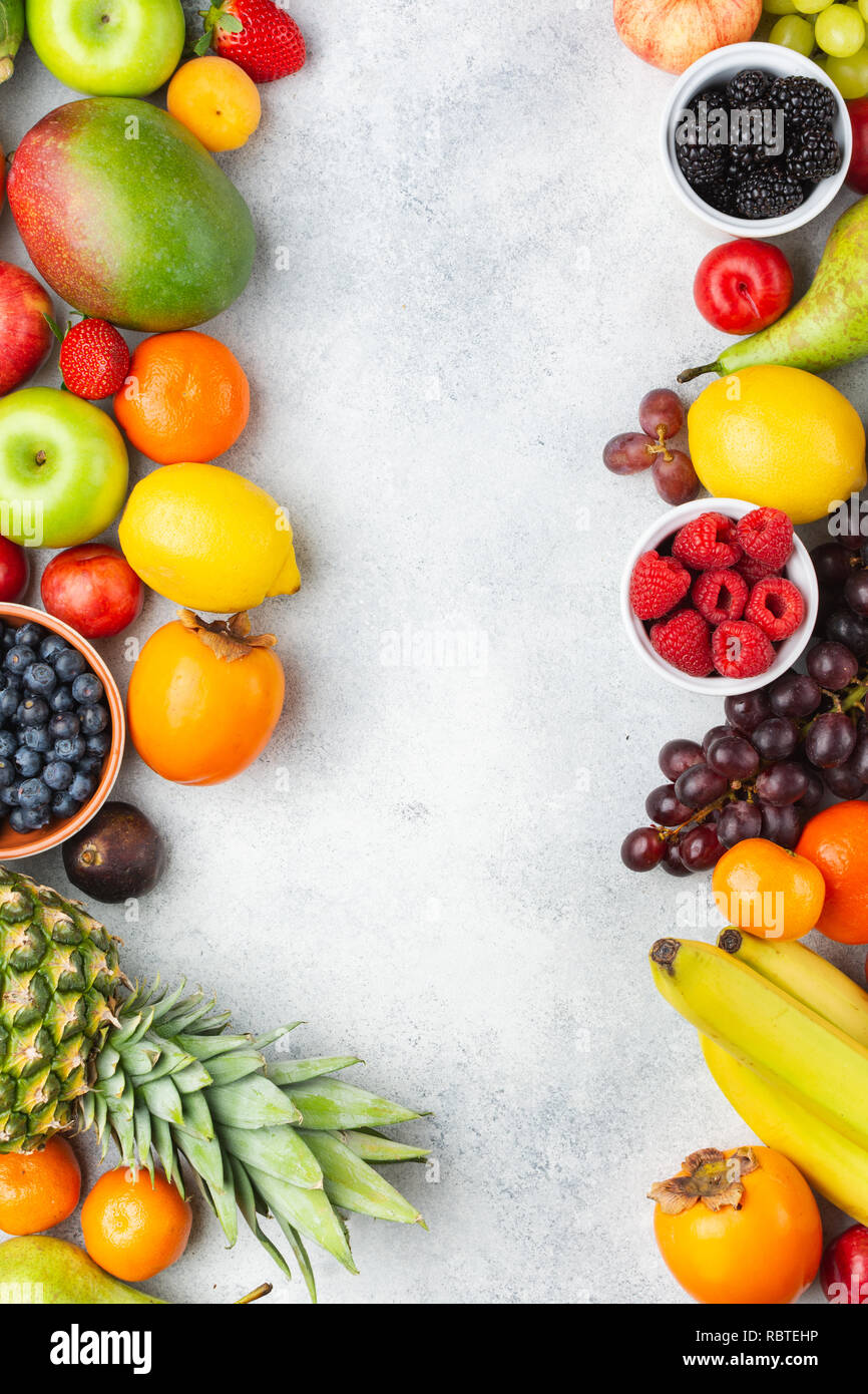 Healthy fruits berries background, strawberries raspberries oranges plums apples kiwis grapes blueberries mango persimmon on the white table - Stock Image