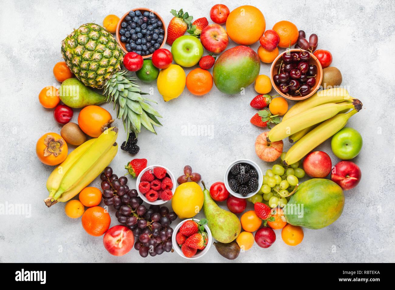 Rainbow fruits background frame, strawberries raspberries oranges plums apples kiwis grapes blueberries mango persimmon on white table, top view - Stock Image