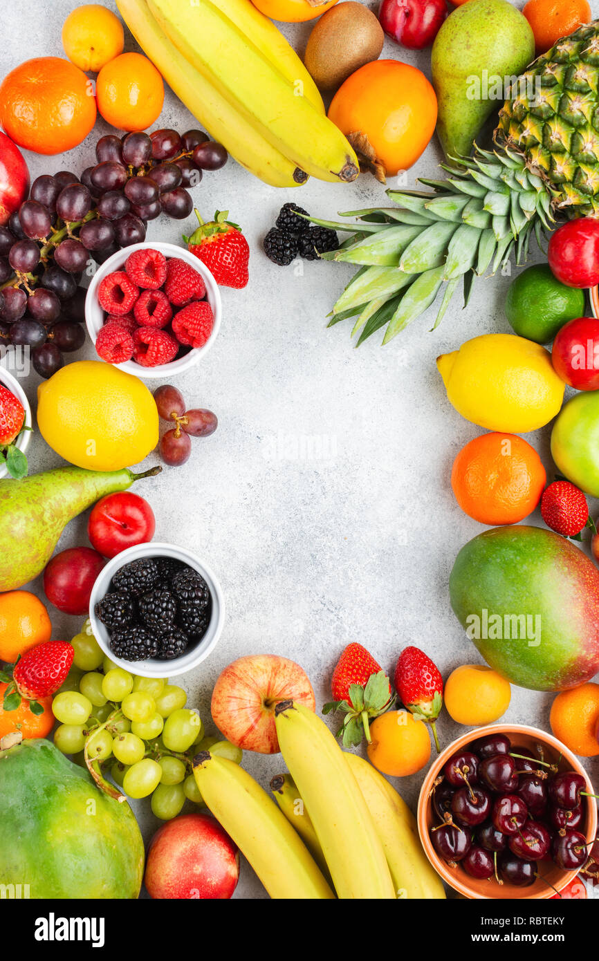 Frame made of ripe fruits, strawberries raspberries oranges plums apples kiwis grapes blueberries mango persimmon on the white table, top view - Stock Image