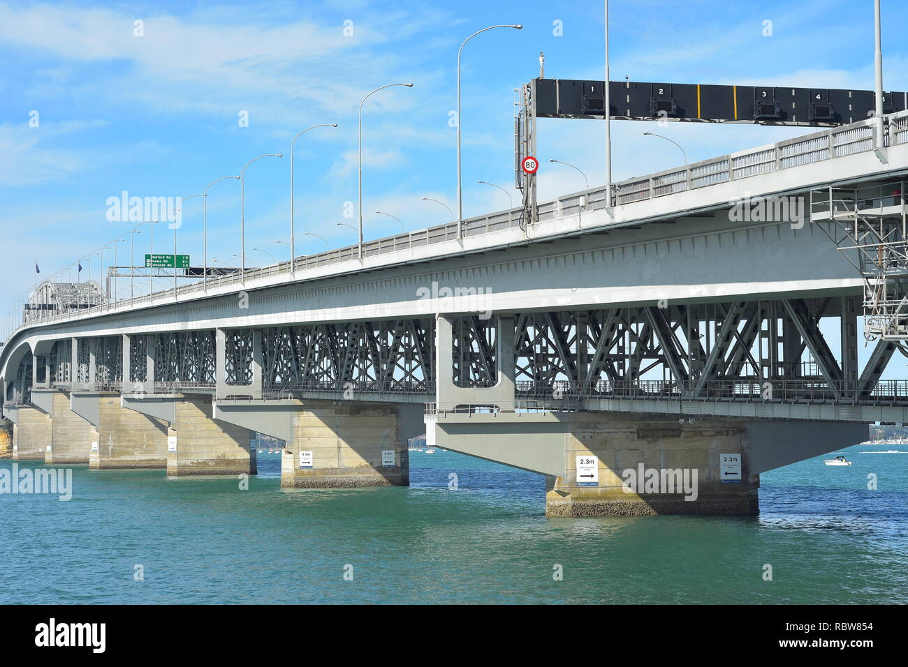 Concrete pylons and steel structure of Auckland Harbour Bridge over Waitemata Harbour from Curran Street on sunny day. - Stock Image