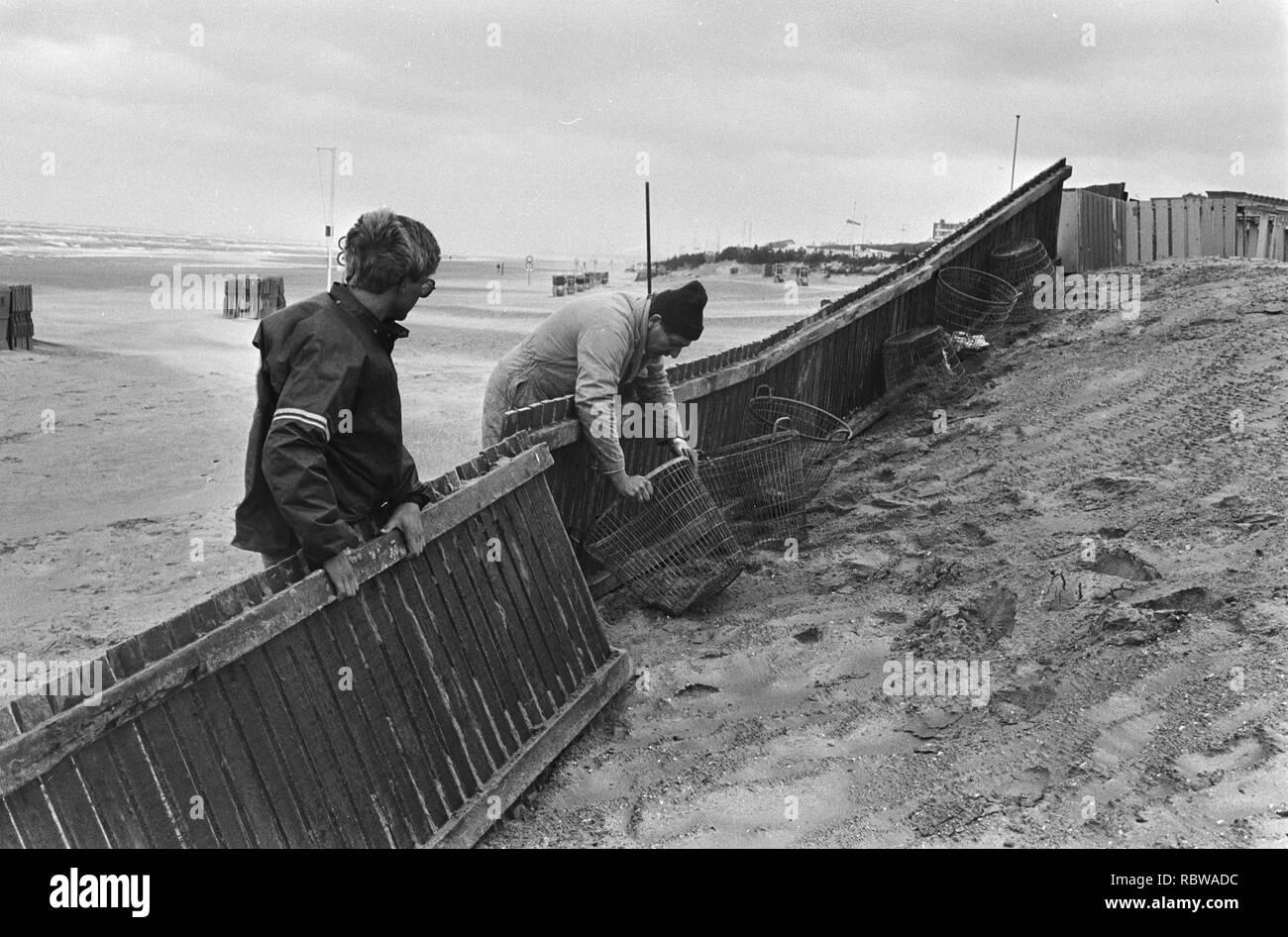 Aanhoudend slecht weer in Nederland strandtenthouder maakt dijk om eigendommen te beschermen tegen het eventuel oprukkende water, Bestanddeelnr 931-5698. Stock Photo