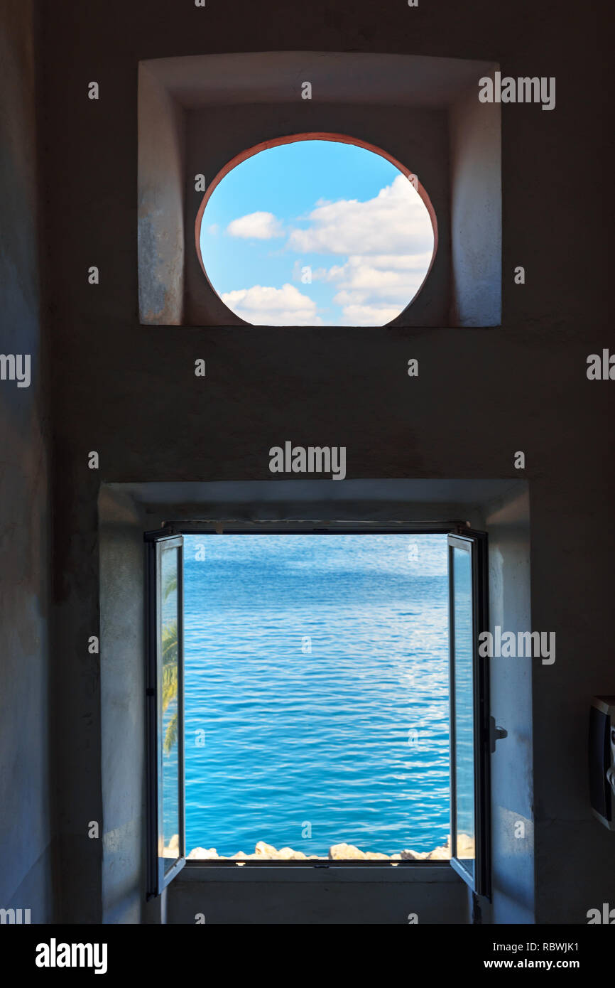 View of the sea and sky through the window. Porto Santo Stefano in Monte Argentario. Tuscany. Italy - Stock Image