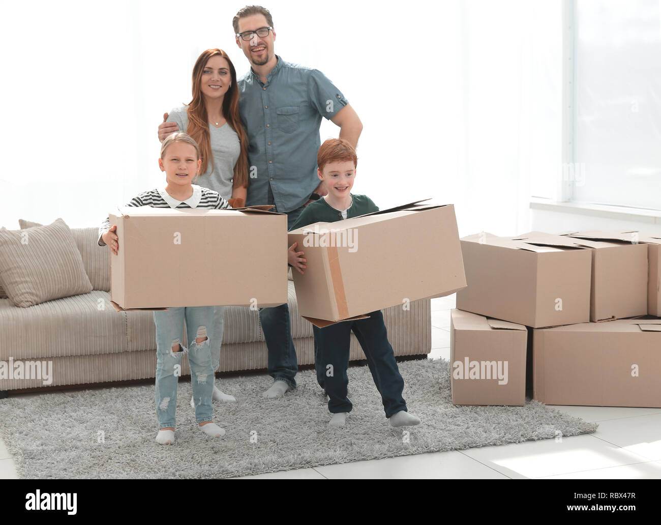 parents with their children moves the boxes to a new apartment - Stock Image