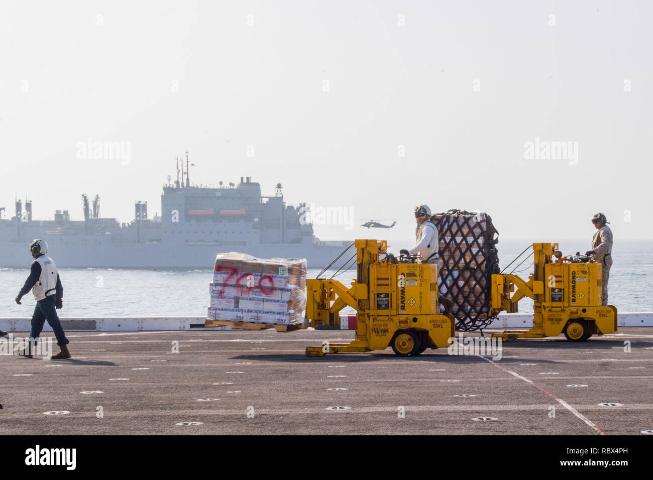 190107-N-PH222-1147 ARABIAN SEA (Jan. 7, 2018) Marines assigned to the 13th Marine Expeditionary Unit (MEU) transport cargo on the flight deck of the San Antonio-class amphibious transport dock ship USS Anchorage (LPD 23) during a vertical replenishment with the dry cargo and ammunition ship USNS Alan Shepard (T-AKE-3), while on a deployment of the Essex Amphibious Ready Group (ARG) and 13th MEU. The Essex ARG/13th MEU is flexible and persistent Navy-Marine Corps team deployed to the U.S. 5th Fleet area of operations in support of naval operations to ensure maritime stability and security in t - Stock Image