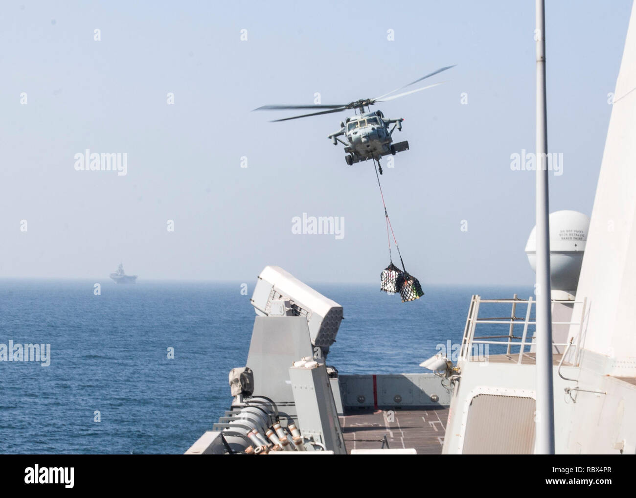 """190107-N-PH222-1933 ARABIAN SEA (Jan. 7, 2018) An MH-60S Sea Hawk helicopter attached to the """"Blackjacks"""" of Helicopter Sea Combat Squadron (HSC) 21, delivers supplies on the flight deck of the San Antonio-class amphibious transport dock ship USS Anchorage (LPD 23) during a vertical replenishment while on a deployment of the Essex Amphibious Ready Group (ARG) and 13th Marine Expeditionary Unit (MEU). The Essex ARG/13th MEU is flexible and persistent Navy-Marine Corps team deployed to the U.S. 5th Fleet area of operations in support of naval operations to ensure maritime stability and security  - Stock Image"""