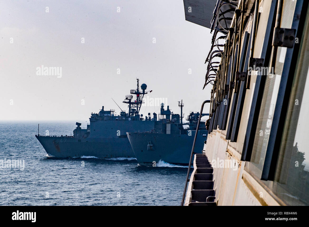 190107-N-PH222-1016 ARABIAN SEA (Jan. 7, 2018) The San Antonio-class amphibious transport dock ship USS Anchorage (LPD 23), right, transits the Arabian Sea, alongside the dry cargo and ammunition ship USNS Alan Shepard (T-AKE-3), center, and the Whidbey Island-class amphibious dock landing ship USS Rushmore (LSD 47), during a vertical replenishment while on a deployment of the Essex Amphibious Ready Group (ARG) and 13th Marine Expeditionary Unit (MEU). The Essex ARG/13th MEU is flexible and persistent Navy-Marine Corps team deployed to the U.S. 5th Fleet area of operations in support of naval  - Stock Image