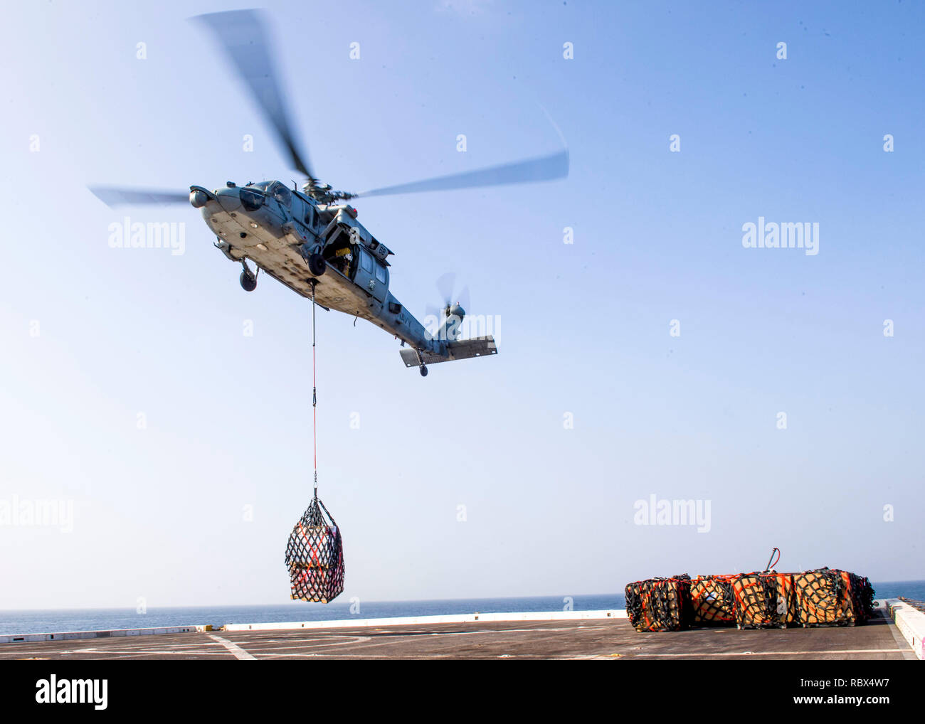 """190107-N-PH222-1116 ARABIAN SEA (Jan. 7, 2018) An MH-60S Sea Hawk helicopter, attached to the """"Blackjacks"""" of Helicopter Sea Combat Squadron (HSC) 21, delivers supplies on the flight deck of the San Antonio-class amphibious transport dock ship USS Anchorage (LPD 23) during a vertical replenishment while on a deployment of the Essex Amphibious Ready Group (ARG) and 13th Marine Expeditionary Unit (MEU). The Essex ARG/13th MEU is flexible and persistent Navy-Marine Corps team deployed to the U.S. 5th Fleet area of operations in support of naval operations to ensure maritime stability and security - Stock Image"""