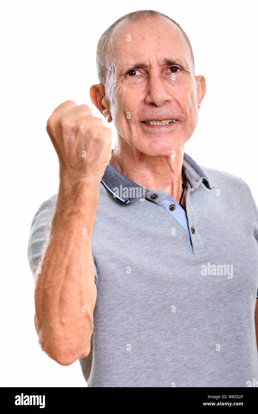 Studio shot of angry senior man with arm raised - Stock Image