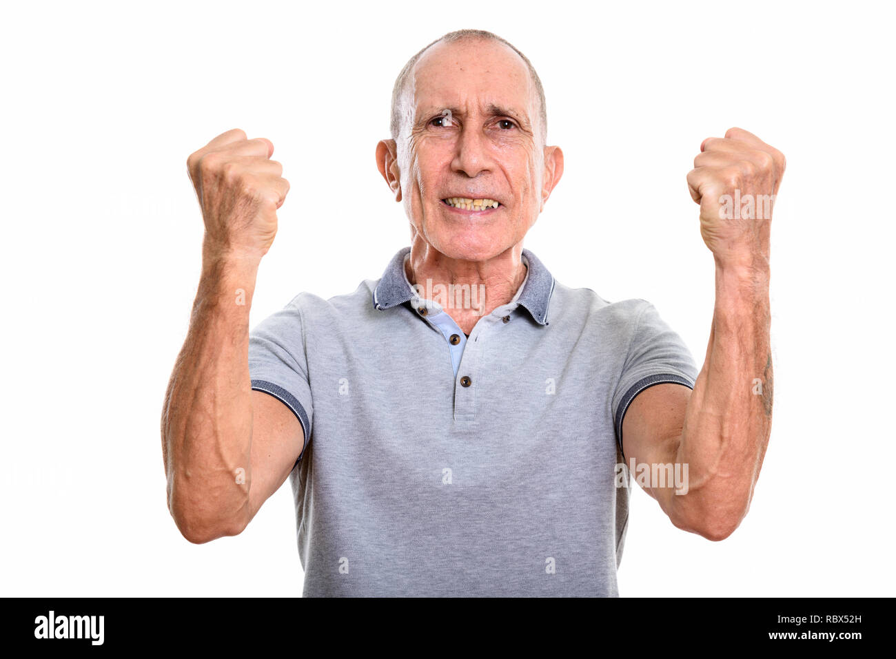 Studio shot of angry senior man with both arms raised - Stock Image
