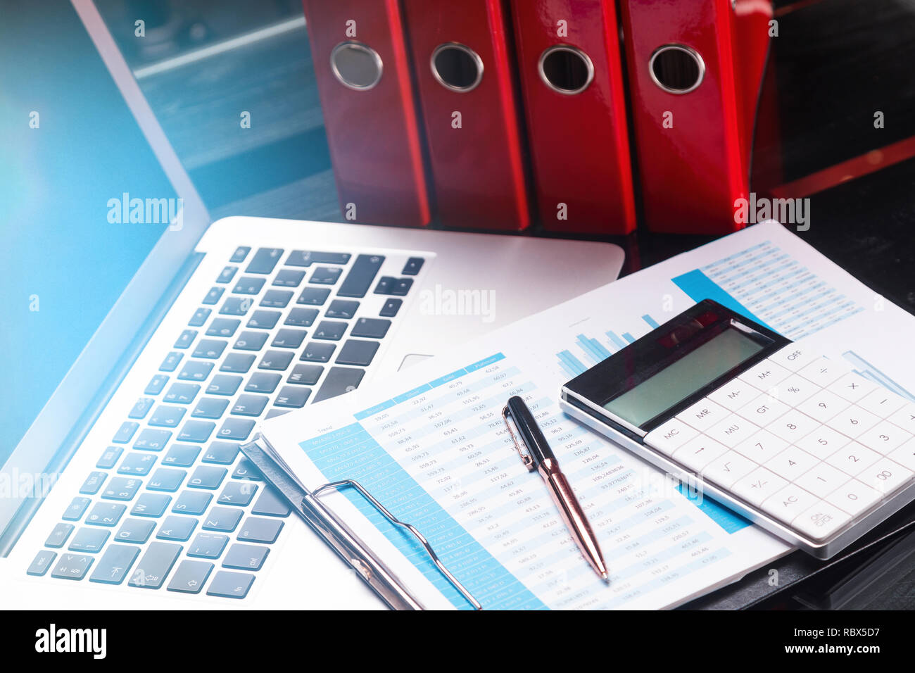 Office workplace with documents and stationery near red folders - Stock Image