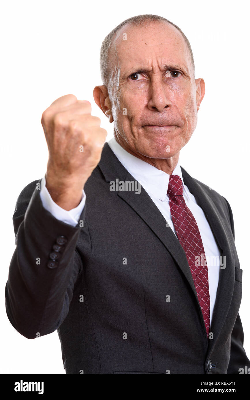 Studio shot of angry senior businessman with fist raised - Stock Image