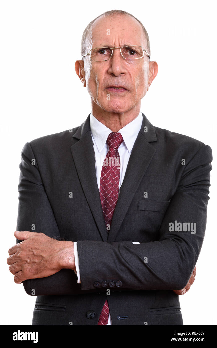Studio shot of angry senior businessman with arms crossed - Stock Image