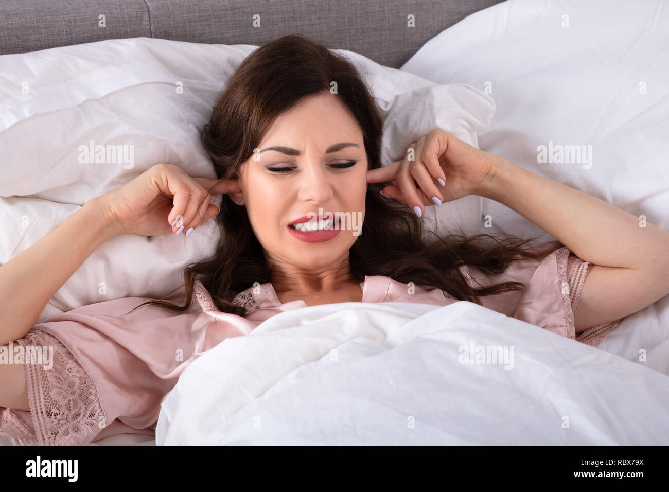 Young Woman Disturbed By Noise Covering Her Ears With Finger - Stock Image
