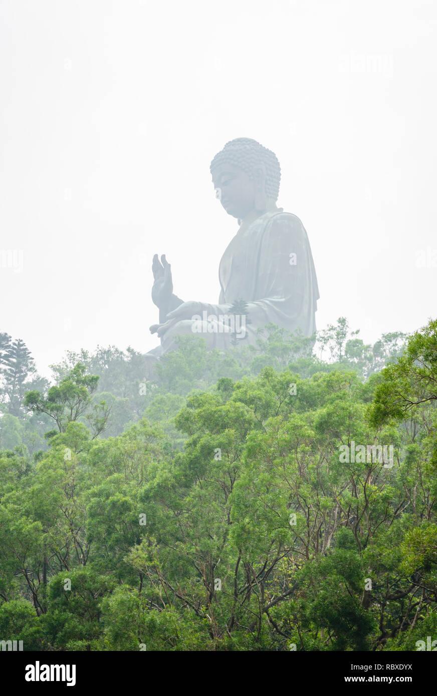 Haze covered Tian Tan Buddha above the tree line, Ngong Ping, Lantau Island, Hong Kong - Stock Image