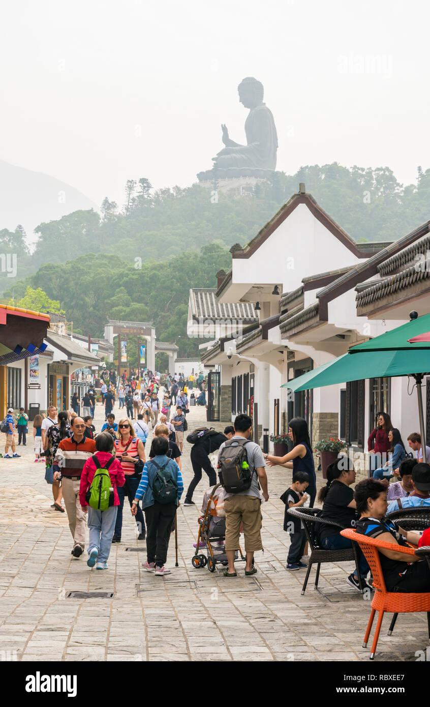 Ngong Ping village overlooked by haze covered Tian Tan Buddha, Lantau Island, Hong Kong - Stock Image