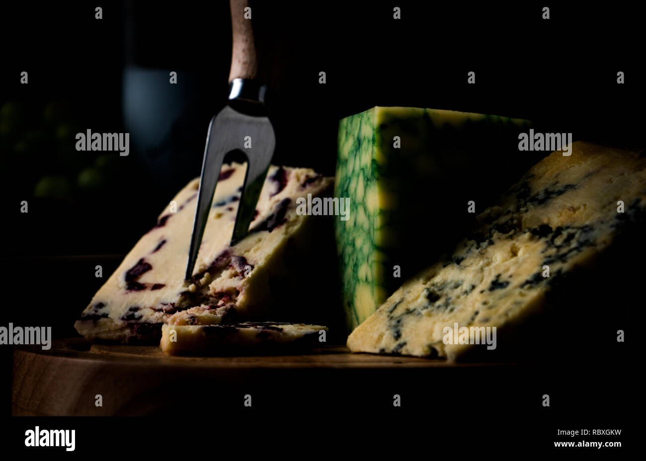 dark mood cheese board selection with Wensleydale, Stilton and Sage Derby against a dark background Stock Photo