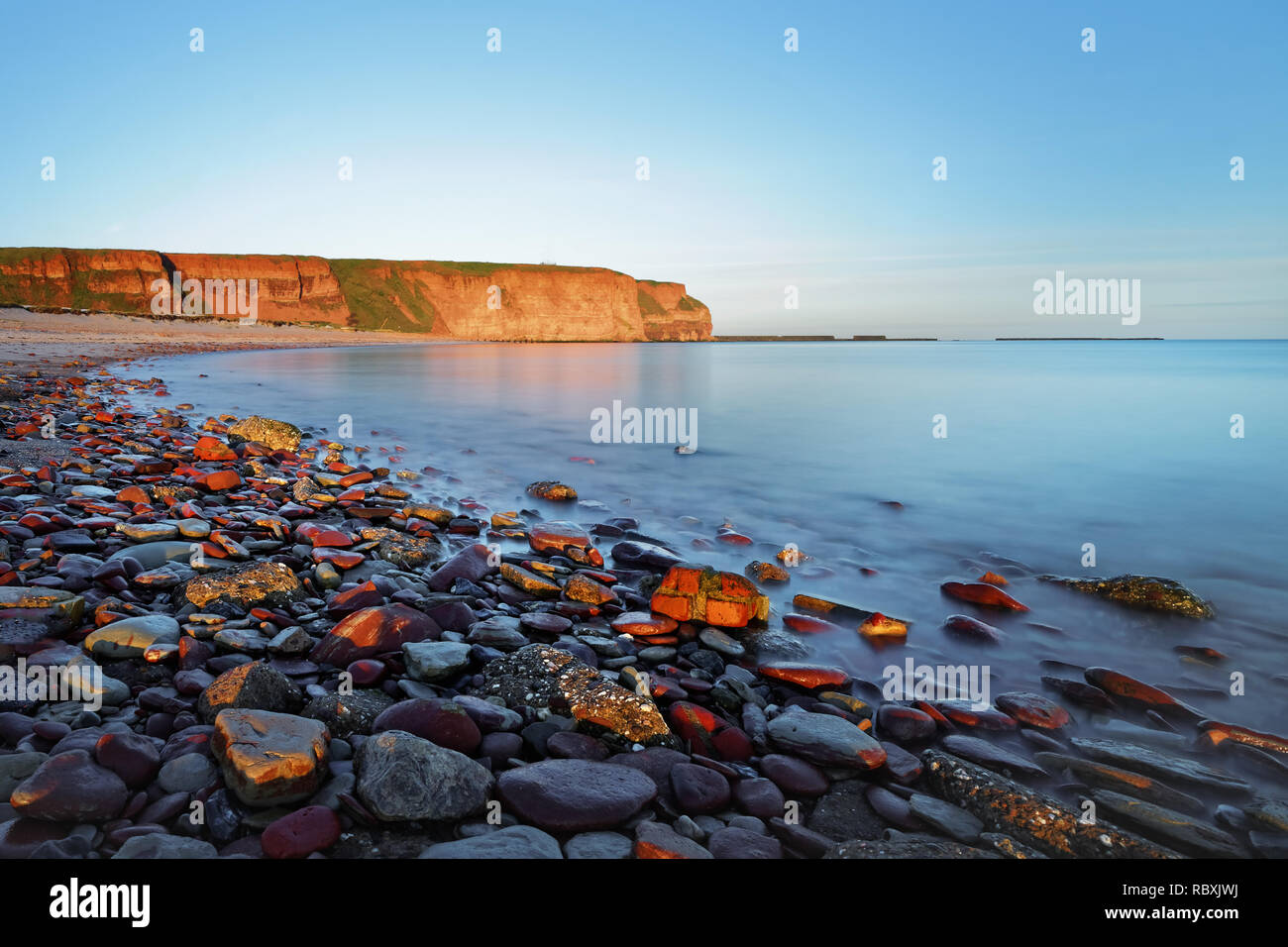 Lonely long beach with different sized stones shortly after sunrise, view to the steep bank, water movement in long exposure, depth effect - Location: - Stock Image
