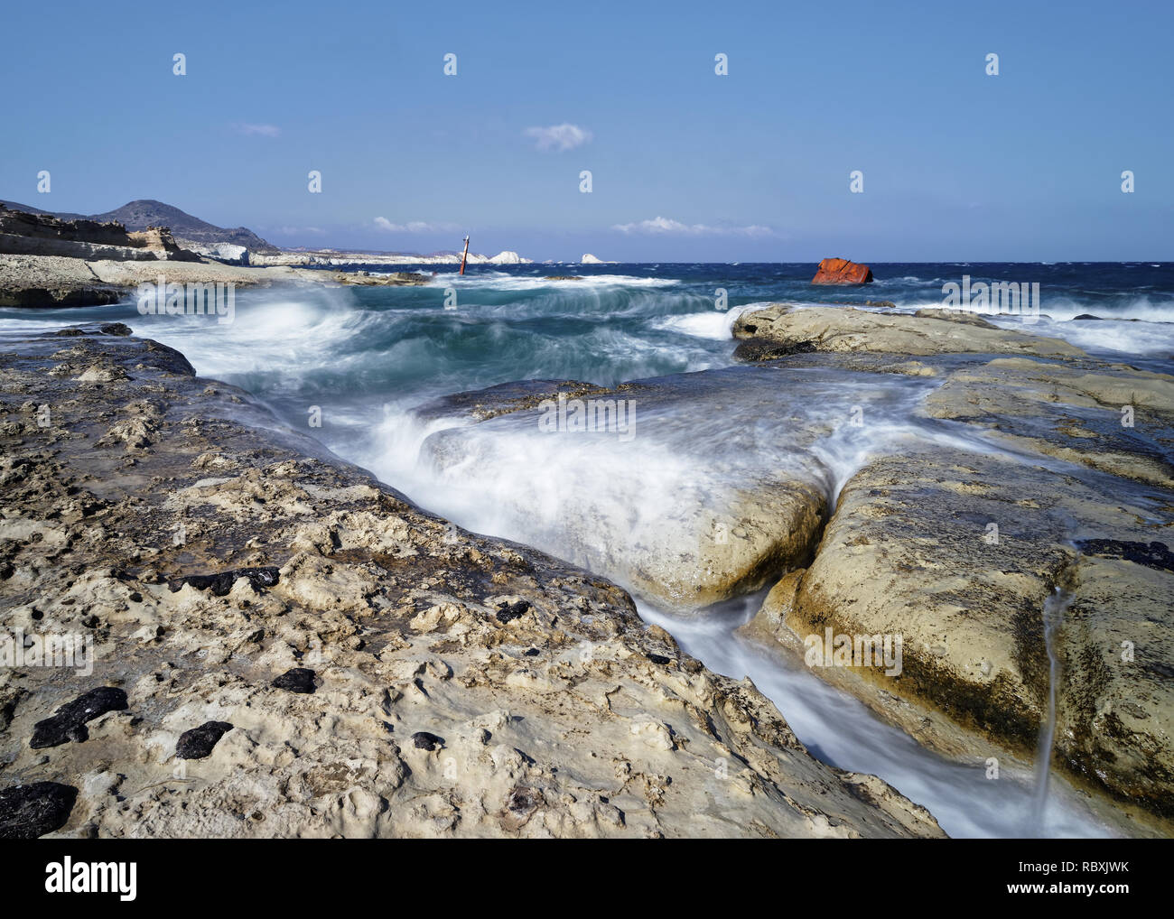 In strong wind high waves flow over large plates on a beach of light rock, water movement in long exposure, in the background a shipwreck - Location:  - Stock Image
