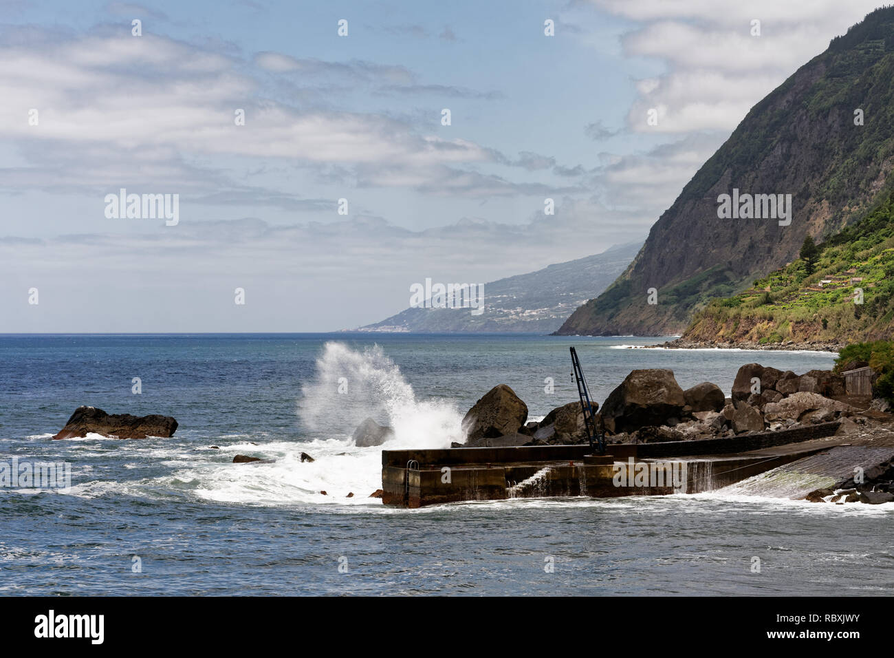 High wave branded in stormy weather at a small pier of the Azores island Sao Jorge, view along the coast - Location: Azores, island of Sao Jorge - Stock Image