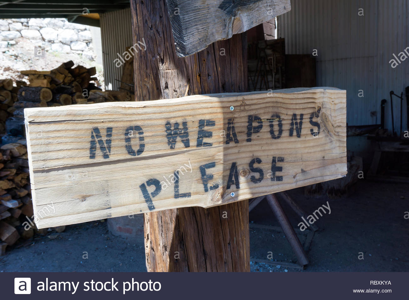 rusti wooden baord sign on a post with the warning 'no weapons' written as instructions before entering in a small town in Arizona - Stock Image