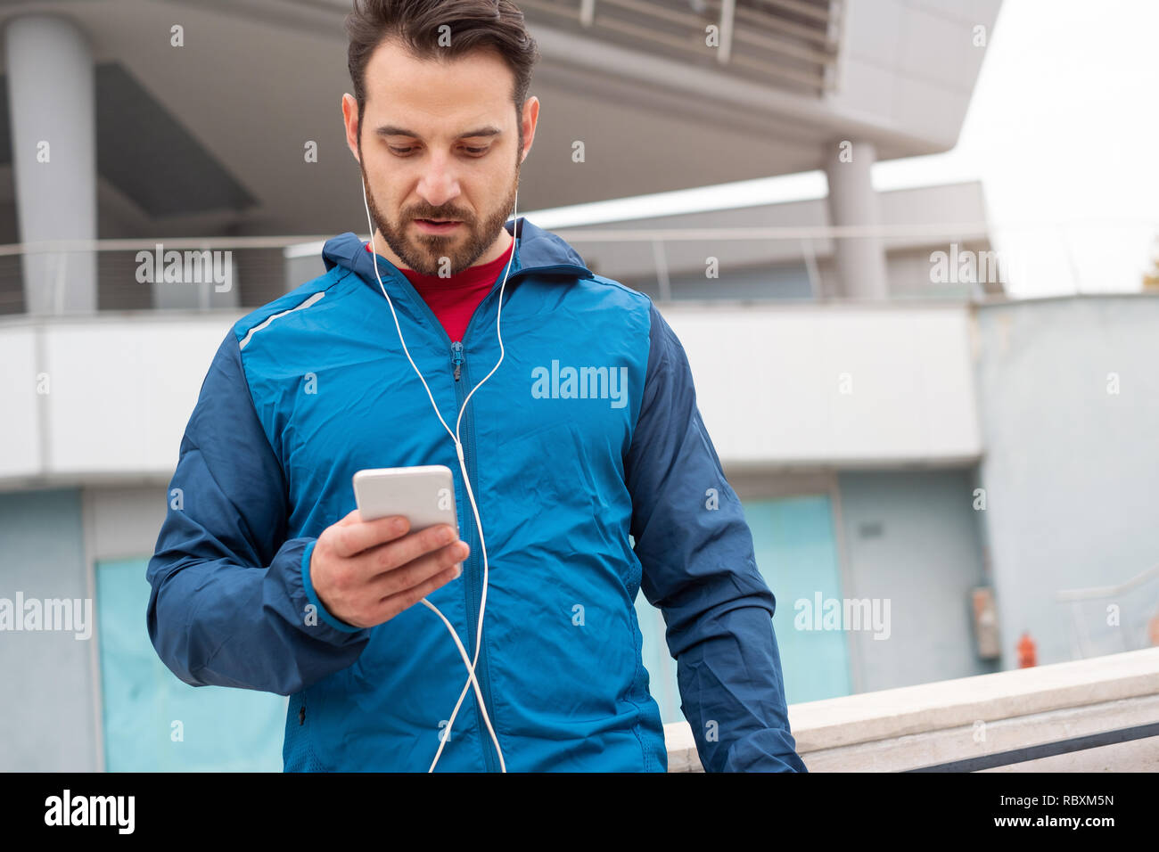 Athletic guy doing training session with smartphone - Stock Image