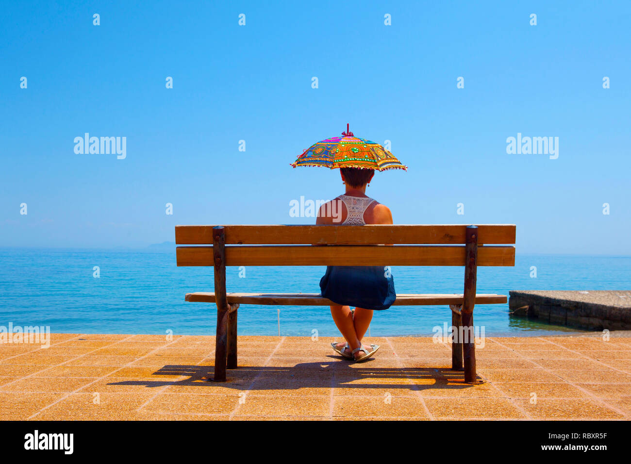 Young woman sitting under a parasol at Poros, Kefalonia, August - Stock Image