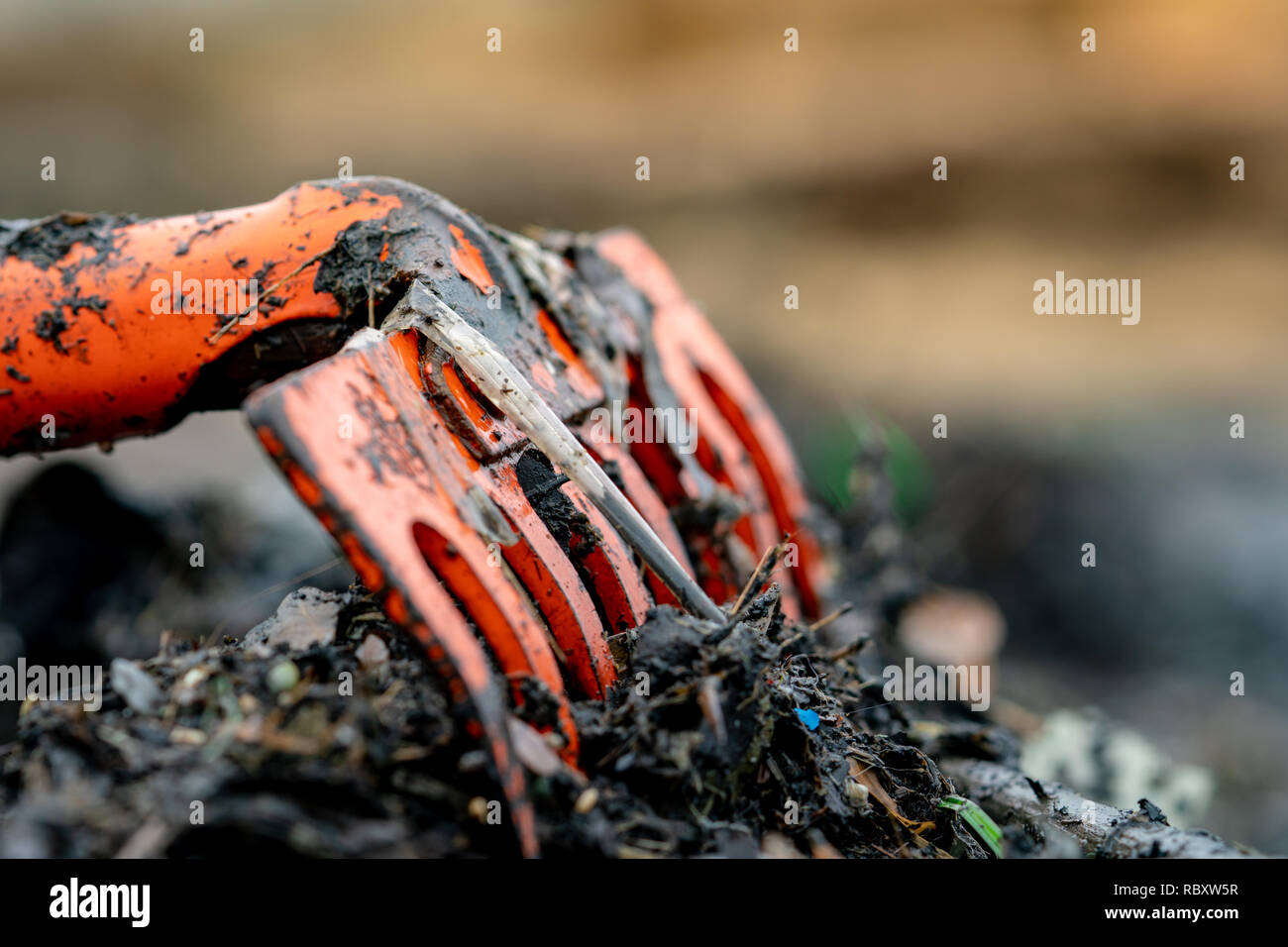 Closeup orange rake on pile of dirty plastic waste on blurred background. Beach environmental pollution concept Clean up rubbish on beach. Ocean - Stock Image
