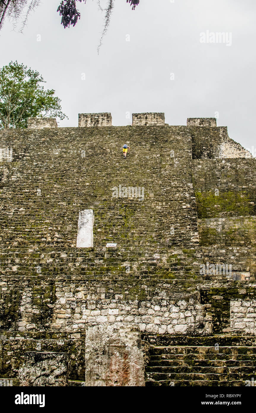 Person climbing an ancient Mayan stones pyramid in Calakmul, Campeche, Mexico - Stock Image