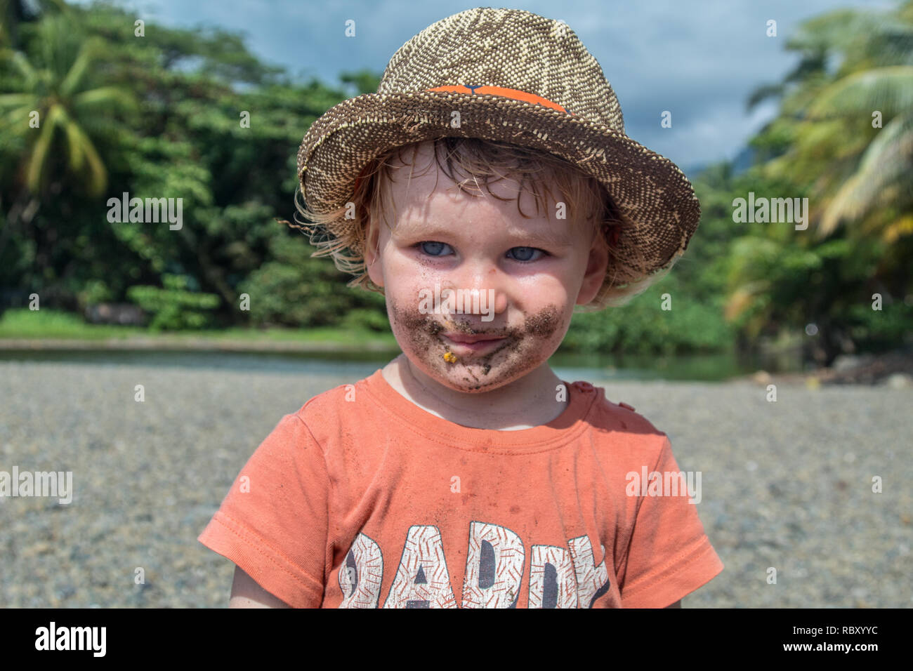 A nice portrait of an adorable toddler who has eaten sand. Mouth is dirty. Jaco Beach, Costa Rica. - Stock Image