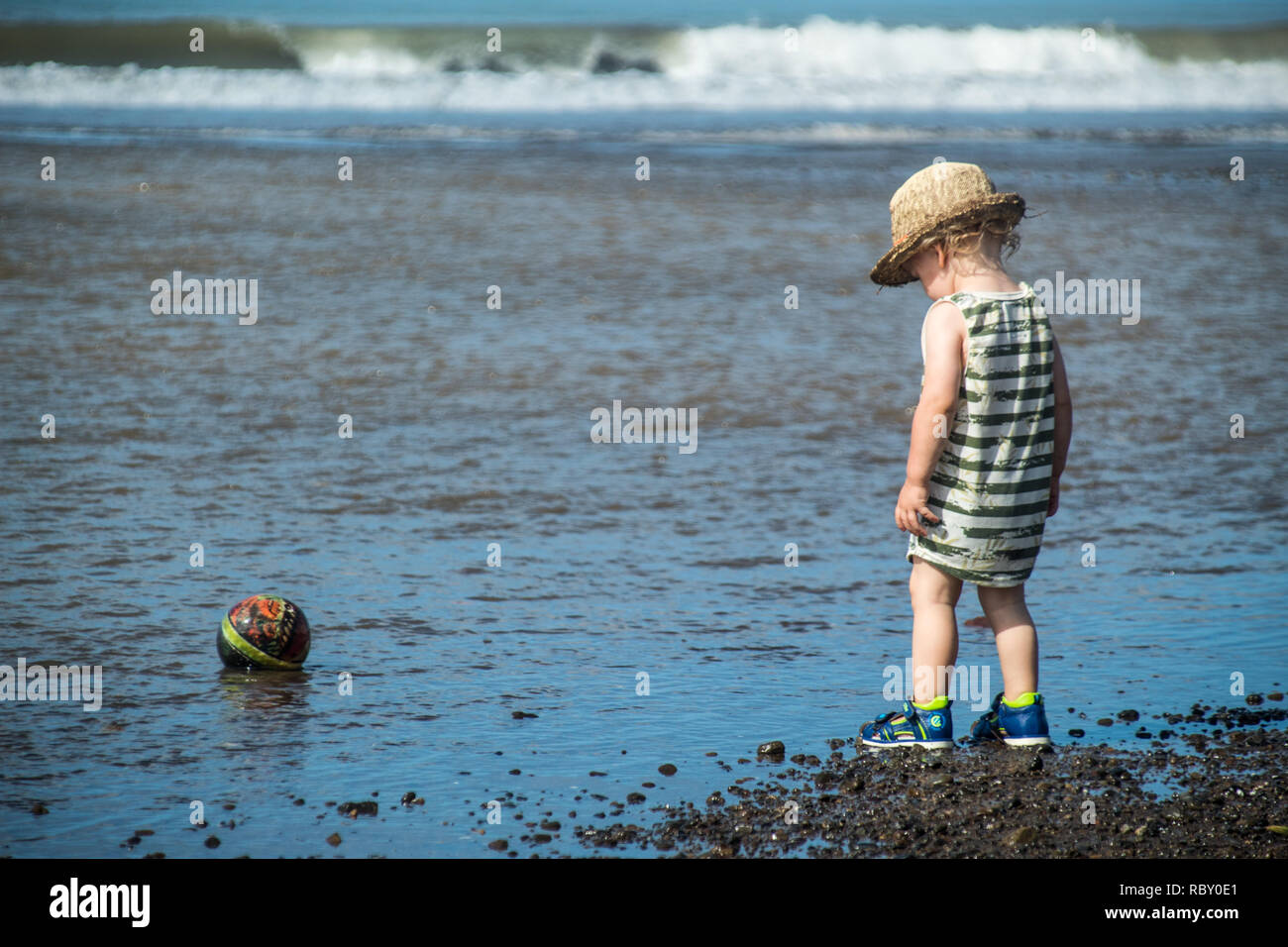 ec93e14296 A photo of a young boy standing at the sea and looking at his ball in the  water