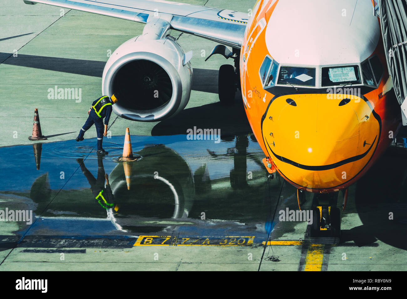 Bangkok, Thailand - October 14, 2018 : member ground crew worker checking aircraft turbine engine, air intake and fan blades of  Nok Air airplane befo - Stock Image