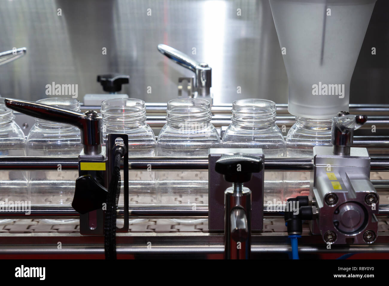 pharmaceutical industry, medicine pills are filling in the plastic bottle on production line machine conveyor at the medical factory. selective focus. - Stock Image