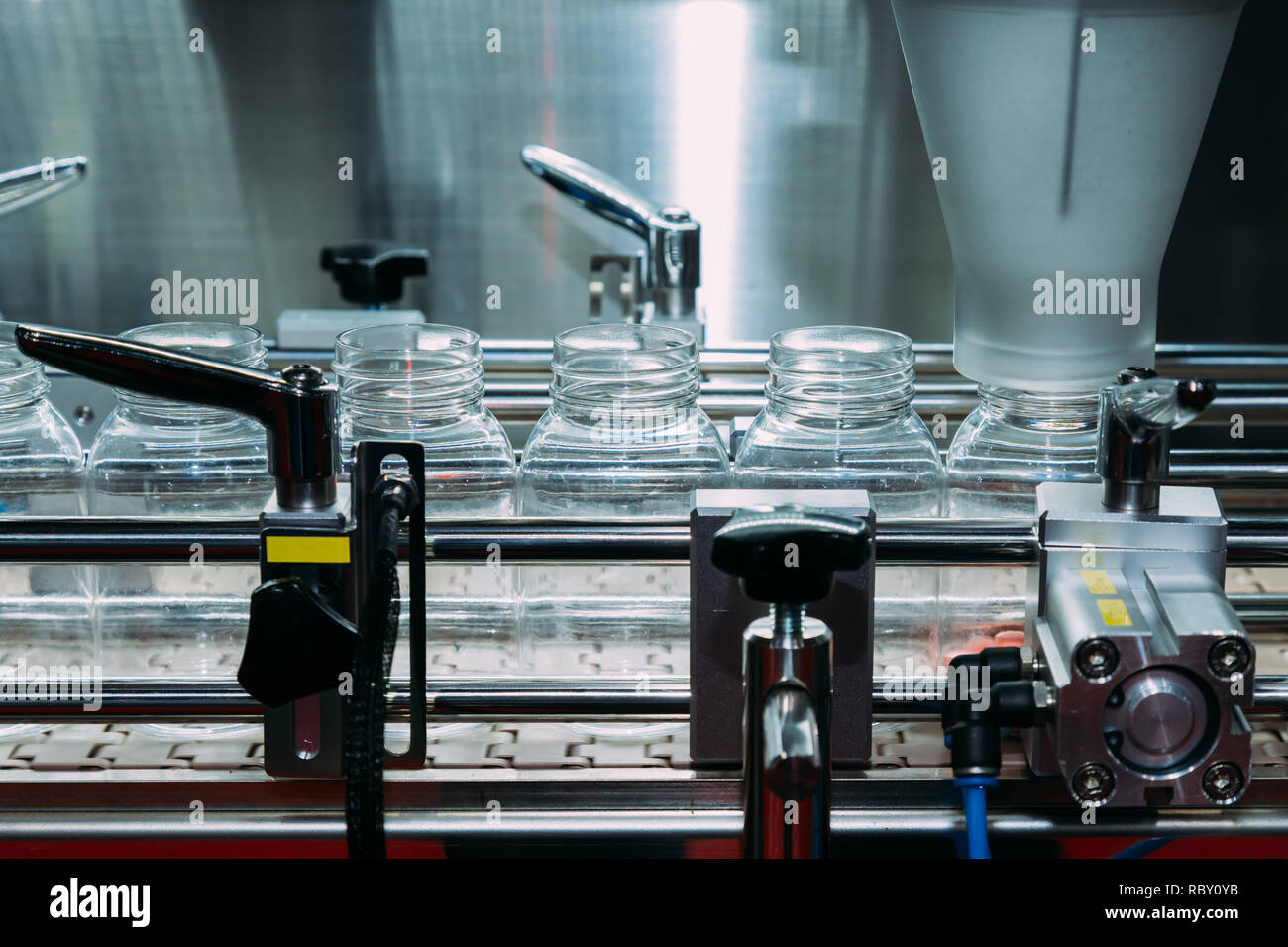 pharmaceutical industry, medicine pills are filling in the plastic bottle on production line machine conveyor at the medical factory. selective focus  - Stock Image