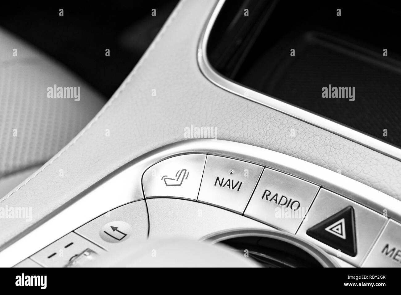 Media and navigation control buttons of a Modern car. Car interior details. White leather interior of the luxury modern car. Car detailing. Black and  - Stock Image