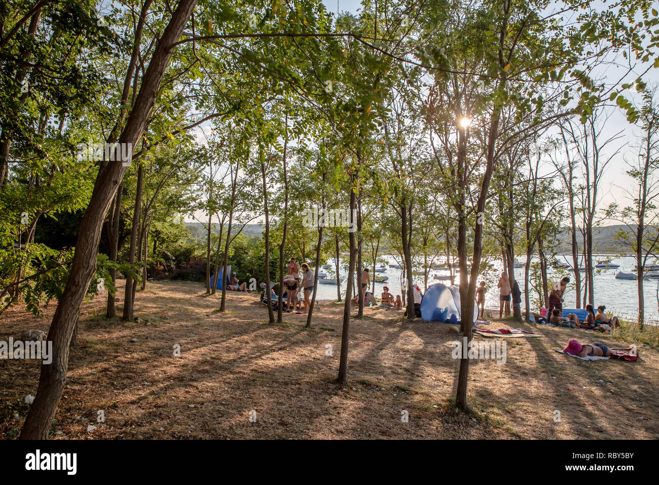 Familes relax on the tree shaded part of the beach at Soline overlooking Soline Bay on the island of Krk, Croatia - Stock Image
