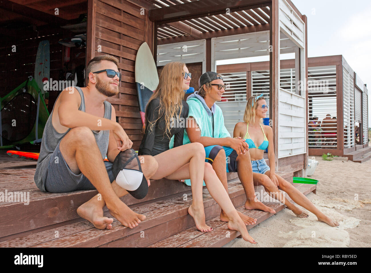 friendship, sea, summer vacation, water sport and people concept - group of friends wearing swimwear sitting with surfboards on beach - Stock Image