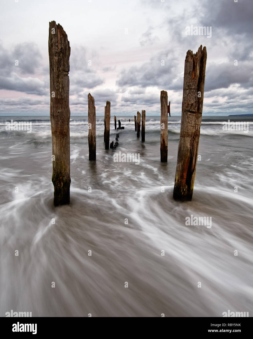 Wooden poles on Baltic Sea beach in high contrast evening light with clouds in windy weather, water movement in long exposure - Location: Baltic Sea,  - Stock Image