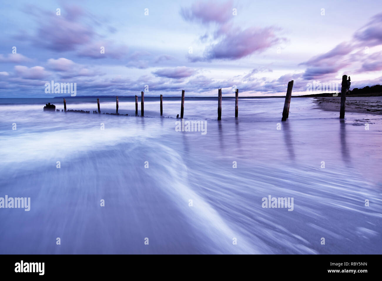 Scenic view of wooden poles on a beach, the movement of the waves is shown in addition to a colorful evening sky - Location: Baltic Sea, Rügen Island - Stock Image