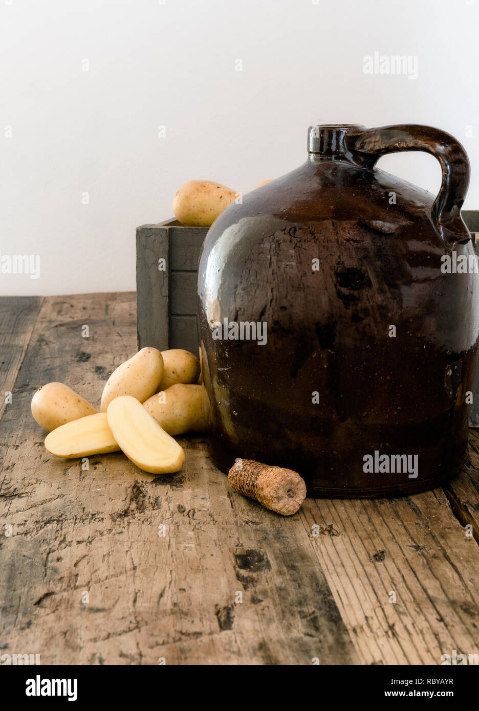 vintage moonshine jug on a rustic wooden table with potatoes and corn cob cork for distilling hard liquor - Stock Image