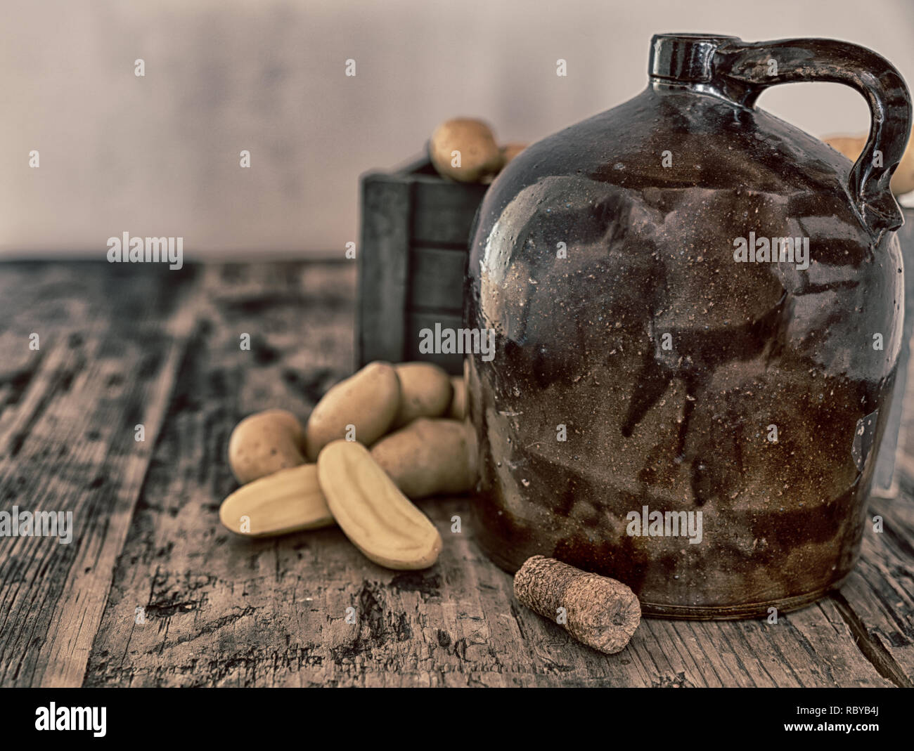 vintage moonshine jug on a rustic wooden table with potatoes and corn cob cork for distilling hard liquor Stock Photo