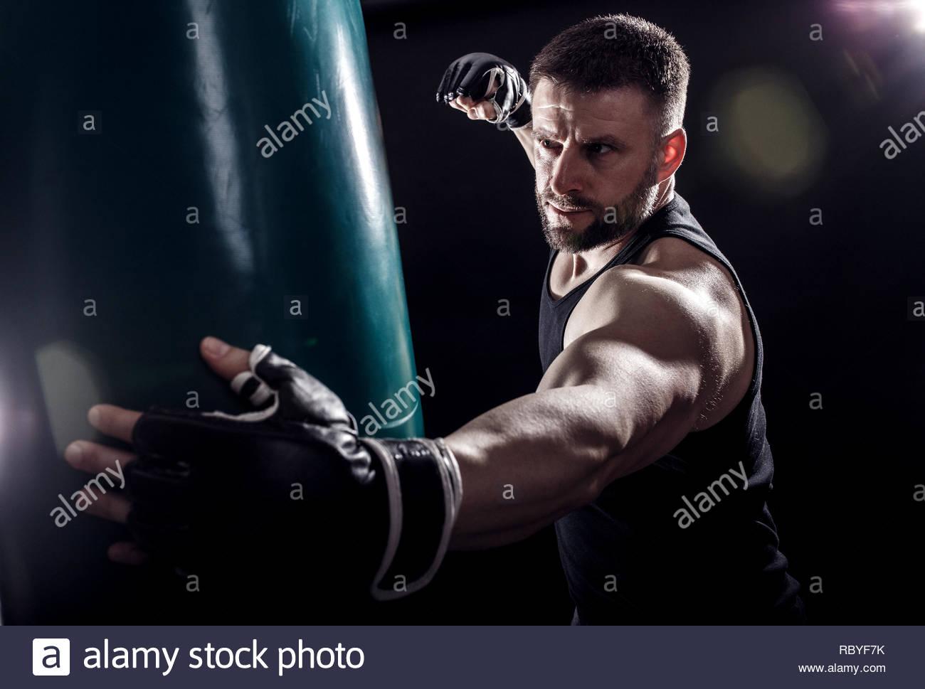 Studio shot of male boxer punching a boxing bag. - Stock Image