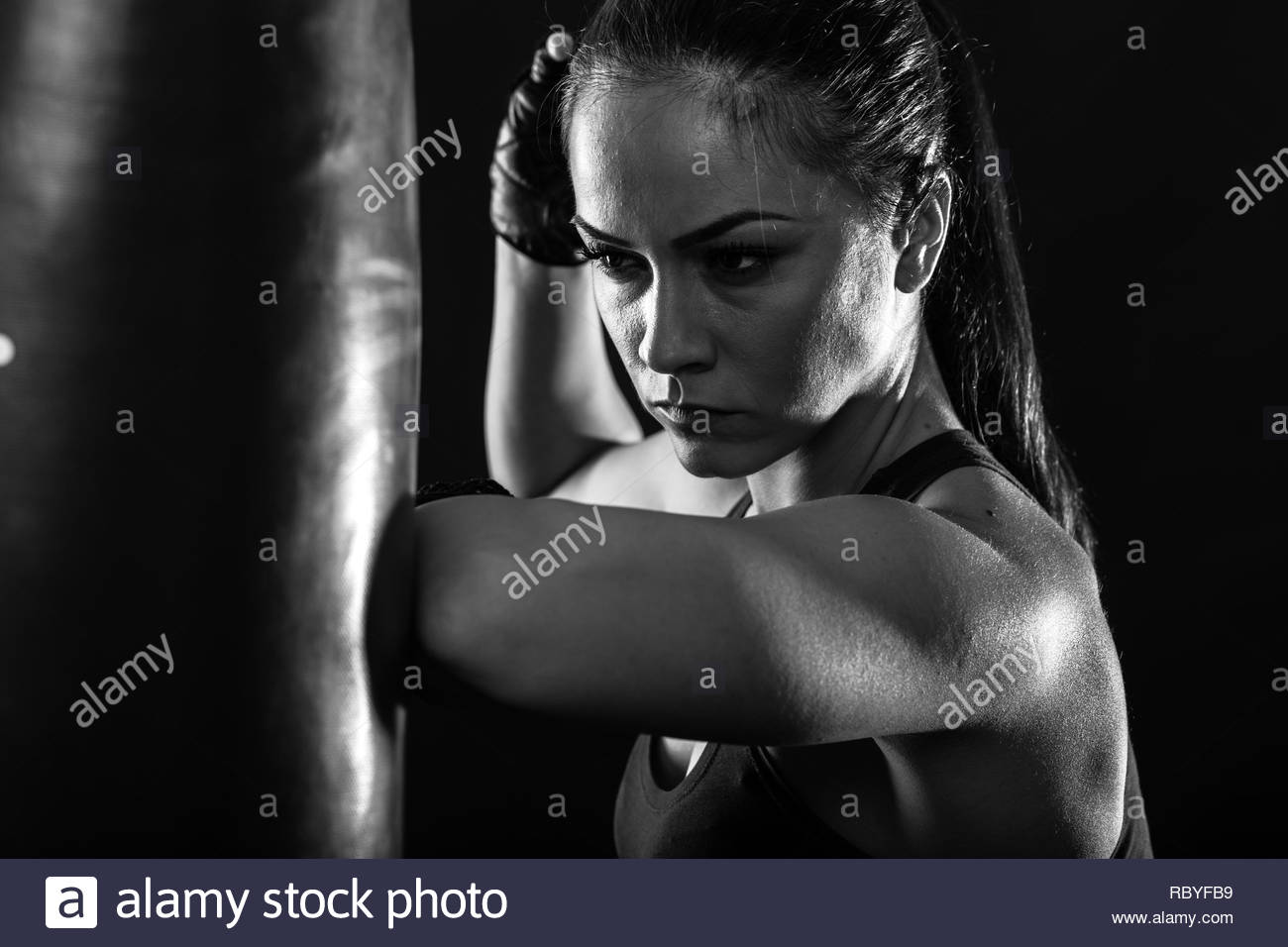 Studio shot of female boxer punching a boxing bag. - Stock Image