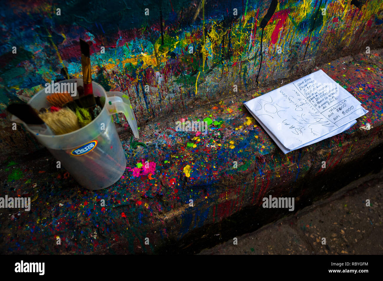 Clean brushes and a poster sketch are seen placed on a splattered kerb in the sign painting workshop in Cartagena, Colombia. - Stock Image