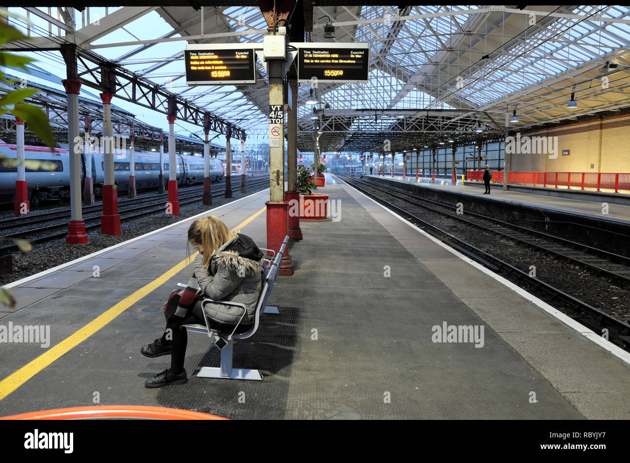 A young woman sitting on a bench waiting for a train on the platform at Crewe railway station in England UK   KATHY DEWITT - Stock Image