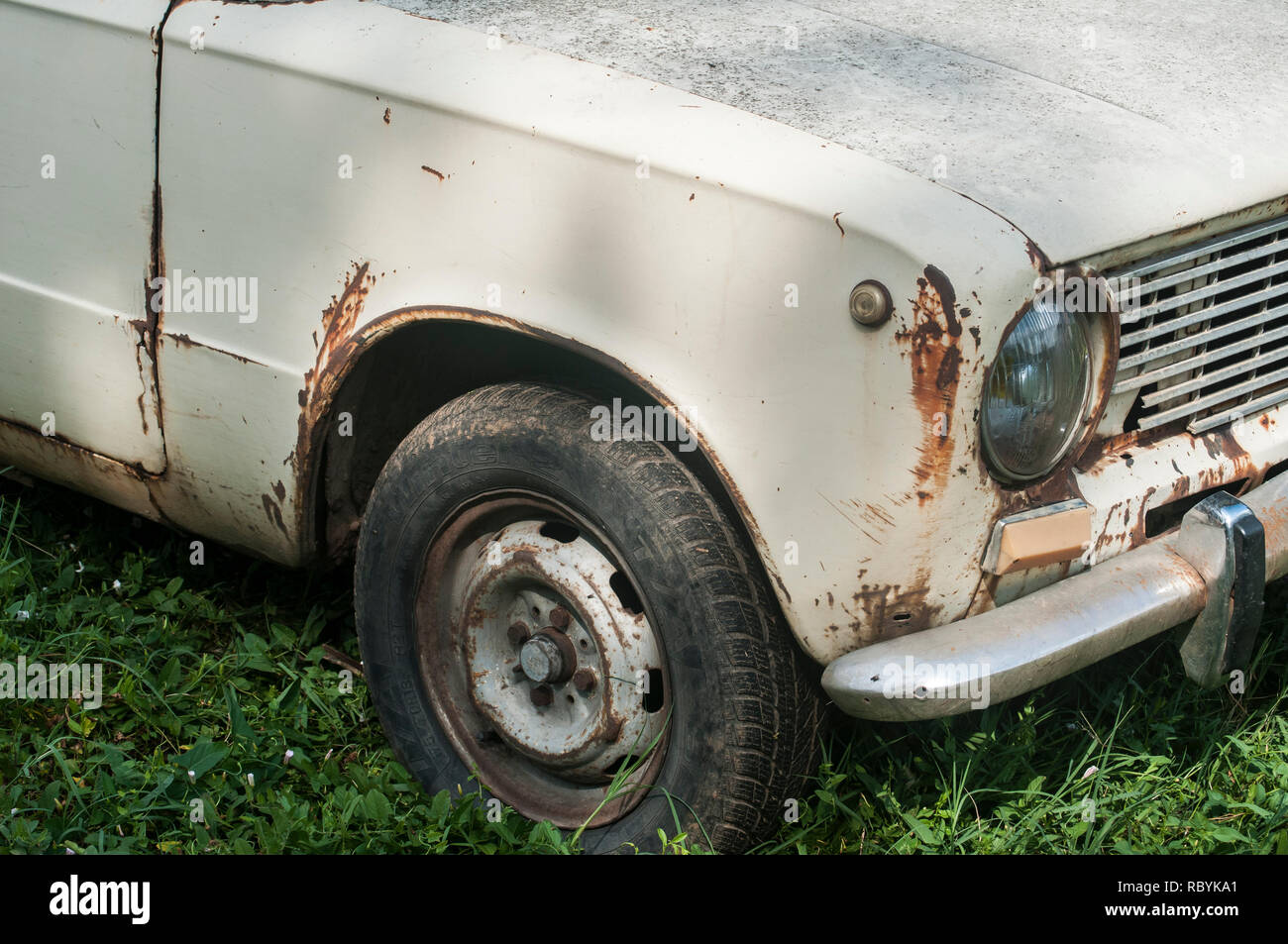 Old weathered abandoned neglected rusty broken vintage obsolete car closeup - Stock Image