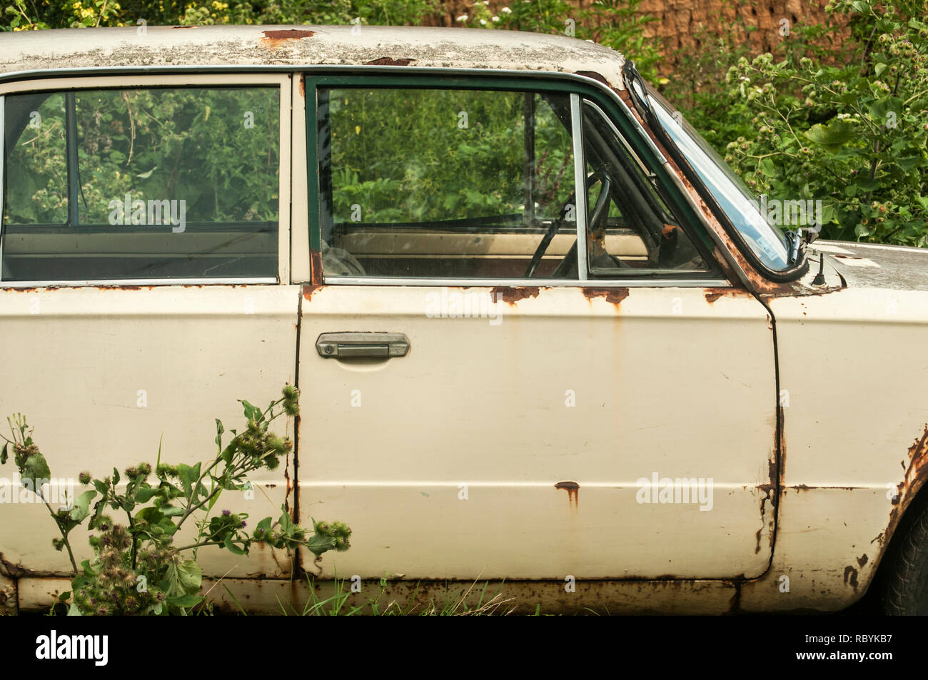 Old weathered abandoned neglected rusty broken vintage obsolete  car closeup in rural place - Stock Image