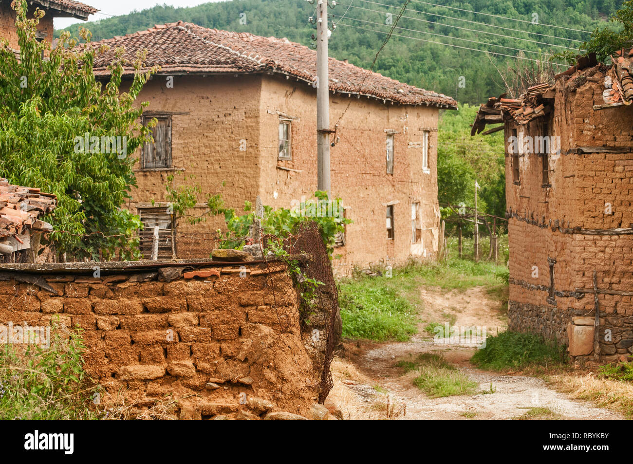 Old abandoned weathered retro vintage rural brick wall houses in countryside village - Stock Image