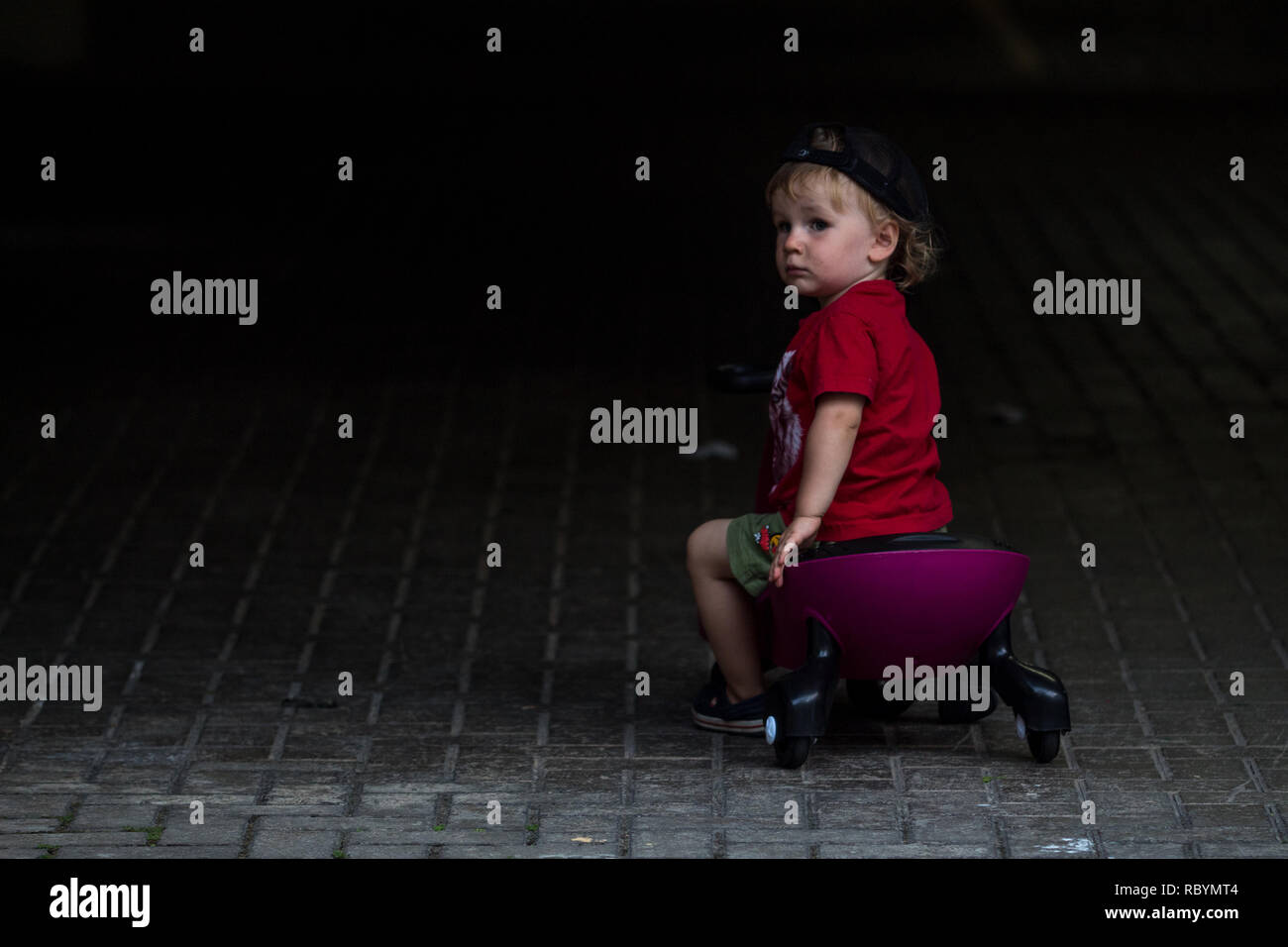 A photo of a kid in a red shirt driving sitting on a purple plasma car like ride on toy looking into darkness - Stock Image