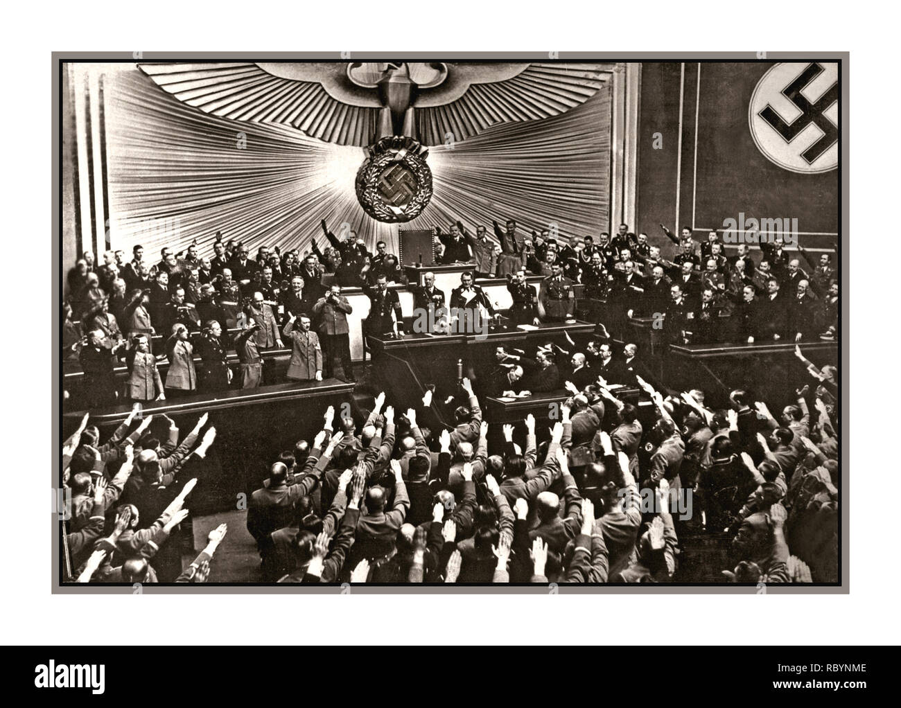 """1938 Adolf Hitler receiving a storm of applause and Heil Hitler salutes from the Reichstag deputies after the announcement of the """"peaceful"""" occupation/ Anschluss of Austria.   Location: Berlin, Germany Date: March 1938 - Stock Image"""