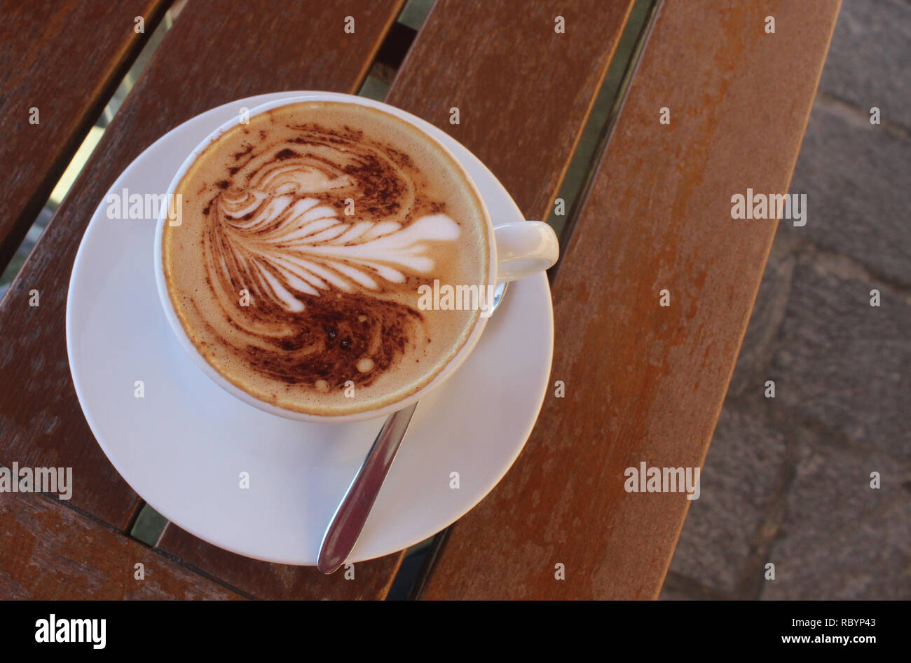 cup of cappuccino on an old wood table, outdoors - Stock Image